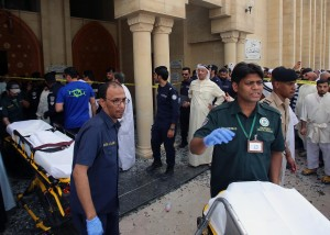 Kuwaiti emergency personnel pull stretchers past security forces outside the Shiite Al-Imam al-Sadeq mosque after it was targeted by a suicide bombing during Friday prayers on June 26, 2015, in Kuwait City. AFP PHOTO / YASSER AL-ZAYYAT